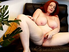 Insolent nude toying in excess of a leather chairperson by a hot chubby redhead