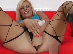 Long legged blonde plays with herself for camera