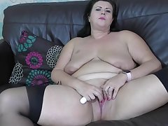 Obese brunette with saggy soul is debilitating black stockings while masturbating like crazy, on the sofa